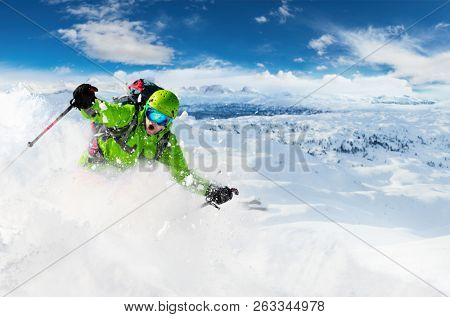 Alpine freeride skier skiing downhill with powder snow explosion. Winter sports and leasure activities