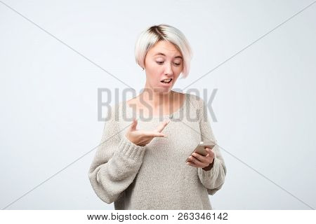 Portrait Of A Shocked Young Girl Looking At Mobile Phone Screen In Surprise Reading Sms