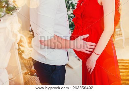 Happy Man Hugging His Pregnant Woman In The Living Room