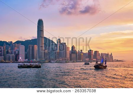 Hong Kong skyline cityscape downtown skyscrapers over Victoria Harbour in the evening with ferry boat and junk boat on sunset. Hong Kong, China