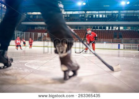 Hockey match at rink boy player in action kicking on goal
