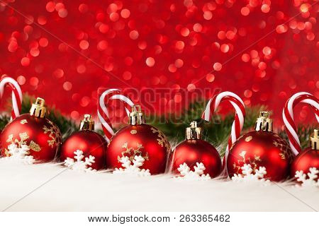 Red Christmas Balls And Candy Decorations On Red Background