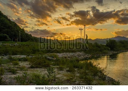 Landscape Of Beautiful Sunset With Puffy Clouds In Sky Over Inlet Shore With A Small Fishing Boat On
