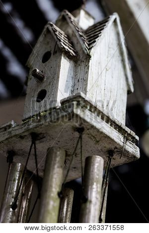 Abstract Bird House Windchime Dirty And Weathered With Moss