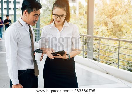 Two Asian Business People Working Together On Digital Tablet At Office Outside.