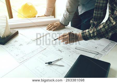 Two Engineering Man Standing Examining Working On Blueprint.