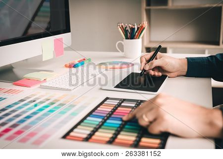 Graphic Designer Working Using Digital Graphic Tablet With Colour Chart And Digitizer At Workplace