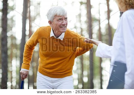 Sick senior man with cane touching his back while talking to clinician on way to hospital poster