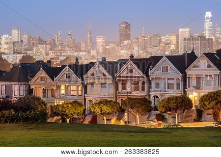 Dusk Over The Painted Ladies Of San Francisco. Iconic Victorian Houses And San Francisco Skyline In