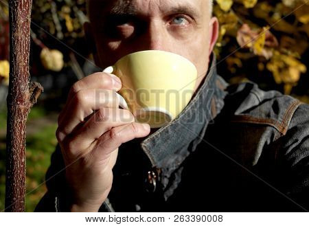 A Man Enjoying Tea Or Coffee While Sitting In A Garden, Contrast Outdoor Portrait