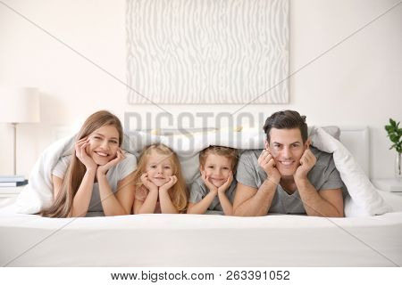 Happy family lying under blanket in bed at home