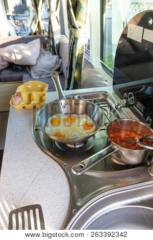 Cooking A Breakfast Of Eggs And Beans In A Campervan
