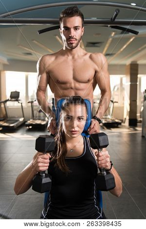 Personal Trainer Showing Young Woman Exercise For Shoulders