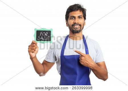 Male Store Owner Or Indian Employee Poiting With Index Finger To For Sale Text On Chalkboard With Fr