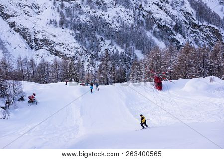 a rescue team with a red helicopter performing the action of rescuing a hurt skier on ski resort