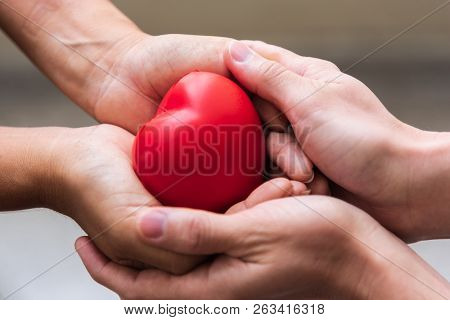 Close Up Hand Giving Red Heart As Heart Donor. Valentine Day Of Love Concept. Medical Ventilator And