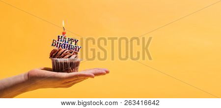 Woman's hand holding decorated birthday muffin against yellow background. Birthday party and celebration.