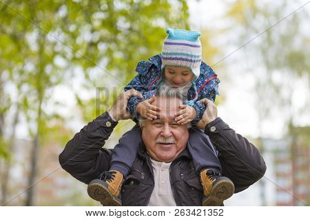 Shot Of A Happy Senior Man Smiling Looking Away His Grandson Hugging Him From Behind Copyspace Relax