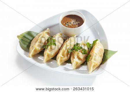 Oriental Fried Dim Sum with Minced Meat also known as Gyoza, Dim Sum, Jiaozi or Momo on a Banana Leaf with Spicy Sauce Close Up. Hot Crunchy Deep-Fried Beef and Mutton Dimsum Isolated on White