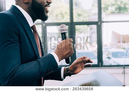 Cropped Image Of Smiling African American Speaker Talking Into Microphone During Seminar In Conferen