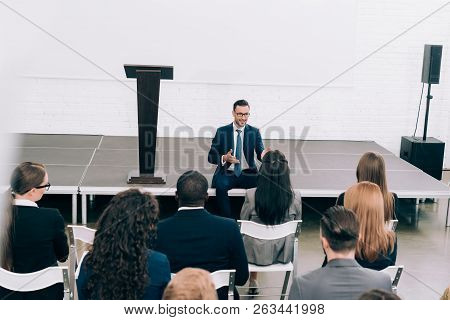 High Angle View Speaker Sitting On Stage During Seminar In Conference Hall And Talking To Multicultu