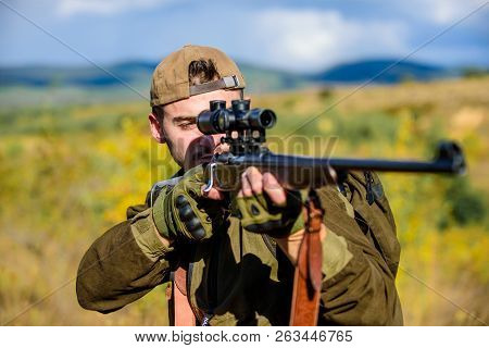 Hunting target. Looking at target through sniper scope. Man hunter aiming rifle nature background. Hunting skills and weapon equipment. Guy hunting nature environment. Hunting weapon gun or rifle poster