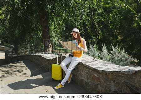 Traveler Tourist Woman In Casual Clothes, Hat With Suitcase Looking On City Map Sitting On Stone In