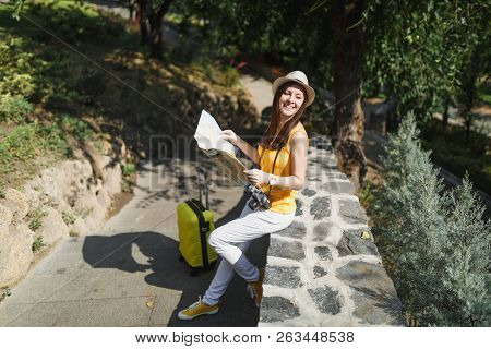 Traveler Tourist Woman In Yellow Clothes Hat With Suitcase Hold City Map Looking Aside Sitting On St