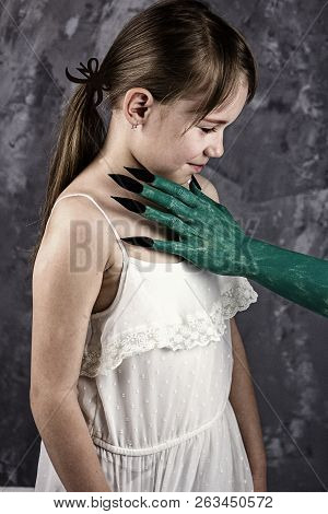 Halloween - Green Witch`s Arms With Black Nails In Front Of The Girl`s Face. The Snow White Fairytal