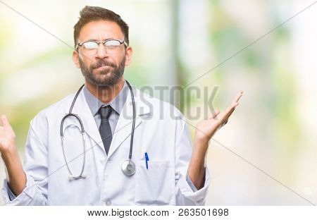 Adult hispanic doctor man over isolated background clueless and confused expression with arms and hands raised. Doubt concept.