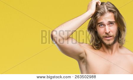 Young handsome shirtless man with long hair showing sexy body over isolated background confuse and wonder about question. Uncertain with doubt, thinking with hand on head. Pensive concept.
