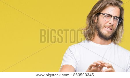 Young handsome man with long hair wearing glasses over isolated background disgusted expression, displeased and fearful doing disgust face because aversion reaction. With hands raised. Annoying