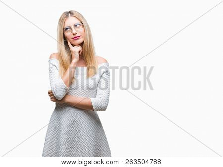 Young beautiful blonde woman wearing glasses over isolated background with hand on chin thinking about question, pensive expression. Smiling with thoughtful face. Doubt concept.