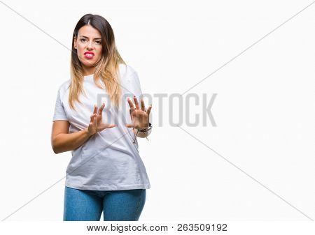 Young beautiful woman casual white t-shirt over isolated background disgusted expression, displeased and fearful doing disgust face because aversion reaction. With hands raised. Annoying concept.
