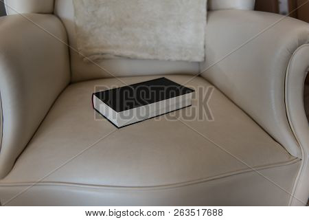 Closed Book Lies On A Leather Chair