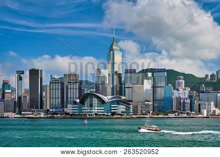 HONG KONG, CHINA - MAY 1, 2018: Boat in Victoria Harbour and Hong Kong skyline cityscape downtown skyscrapers over in the day time with clouds. Hong Kong, China.