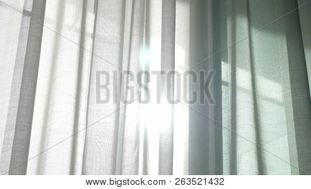 A Transparent Curtain On The Window, Gently Moved By The Wind. Sunlight