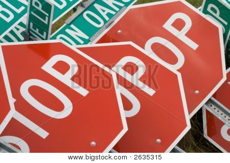 Stop signs piled up on a construction site poster