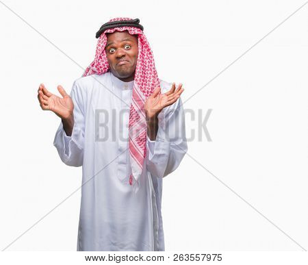 Young arabic african man wearing traditional keffiyeh over isolated background clueless and confused expression with arms and hands raised. Doubt concept.
