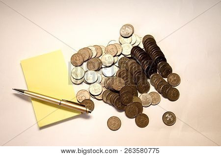 Yellow Notebook With Pen And Mountain Of Mettalical Coins On White Background