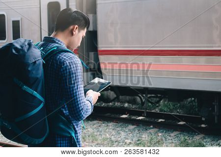 Smart Young Asian Man Using Tablet At Train Station.