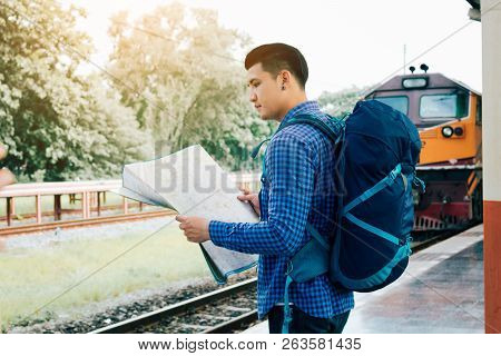 Asian Man Holding Map Paper And Looking Router With Plan For Travel At Train Station.