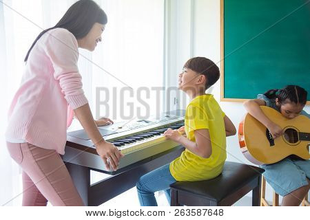 Beautiful Asian Female Teacher Teaching Kids Playing Music Instruments In School Classroom