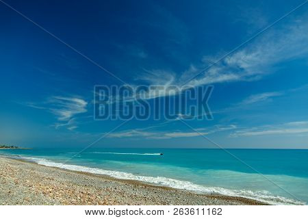 Idyllic Stone Beach With Water Jet And Blue Sky