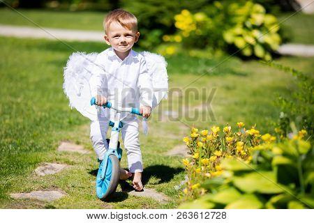 Toddler Boy Wearing Angel Wings Riding A Balance Bike (run Bike), Learning To Keep Balance On A Trai