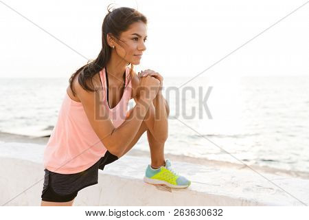 Photo of energetic sporty woman 20s in tracksuit stretching legs during workout at seaside