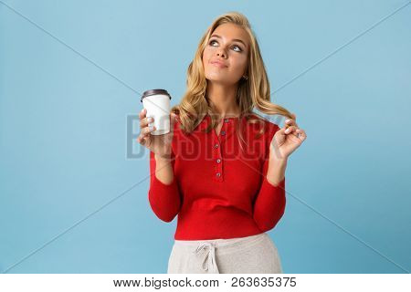 Portrait of excited blond woman 20s wearing red shirt holding takeaway coffee isolated over blue background in studio poster