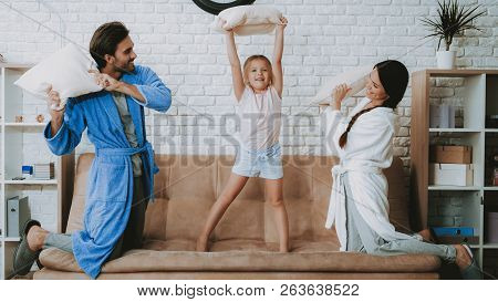 Happy Family Morning. Fight With Pillows Parents And Daughter. Family Resting Together. Man And Woma