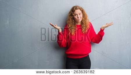 Young redhead woman over grey grunge wall wearing red sweater clueless and confused expression with arms and hands raised. Doubt concept.