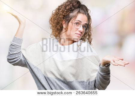 Beautiful brunette curly hair young girl wearing glasses over isolated background clueless and confused expression with arms and hands raised. Doubt concept.